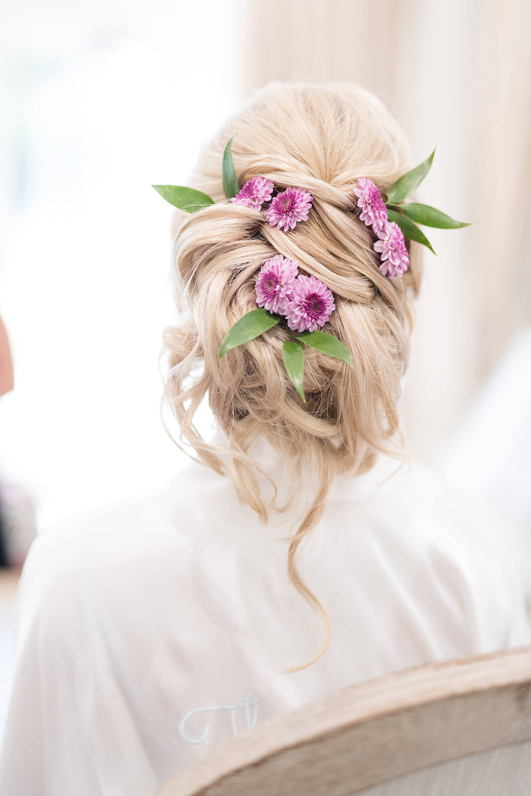 bridal whimsical hair updo with purple flowers