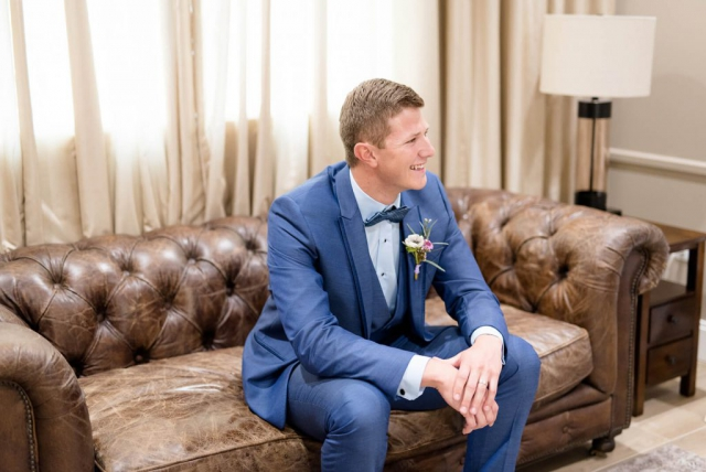 Groom in blue suite, brown leather couch in groom suite