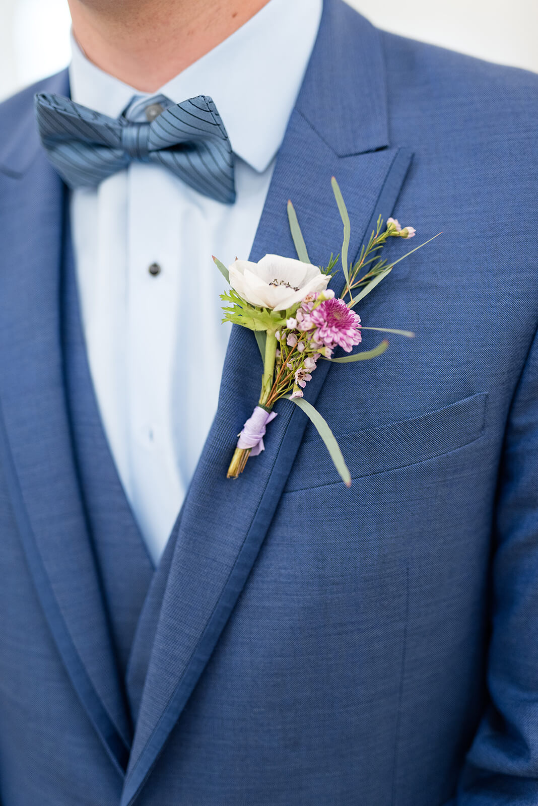 Groom in blue suite with blue bow tie