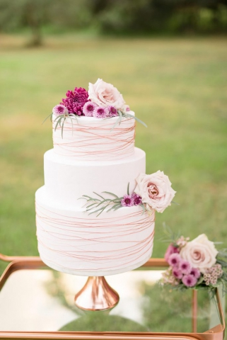 white cake with copper trim and purple floral
